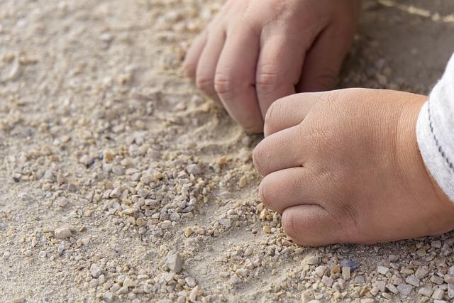 Babyhände im Sand