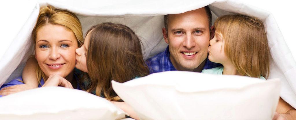 Glückliche Familie liegt unter Bettdecke