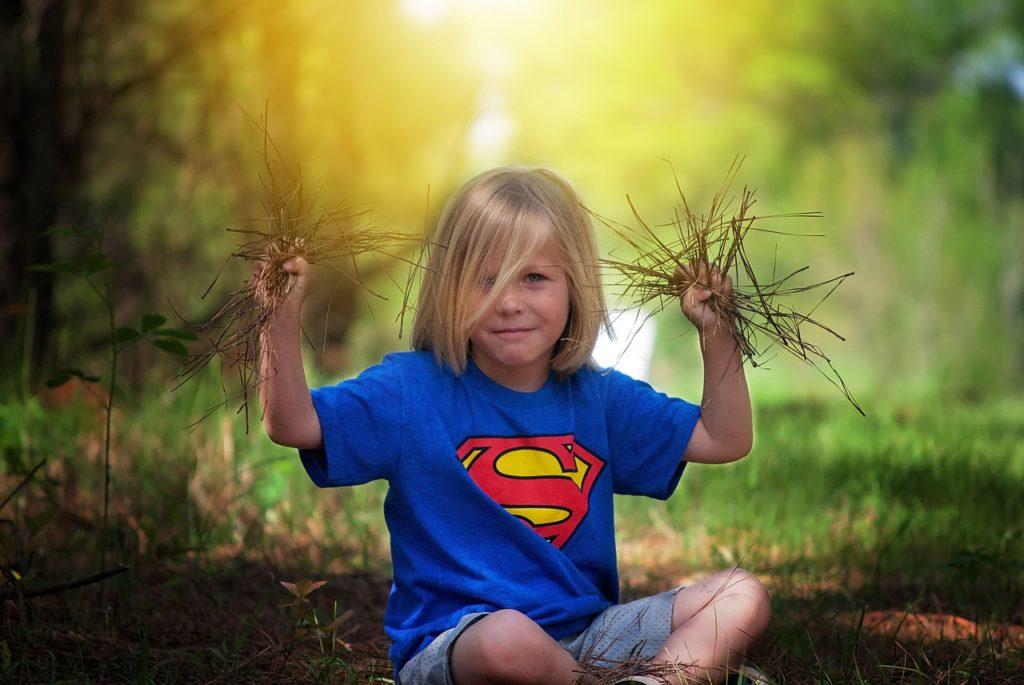 Junge hällt Gras in beiden Händen