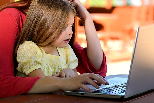 Nanny mit Mädchen vor dem Computer