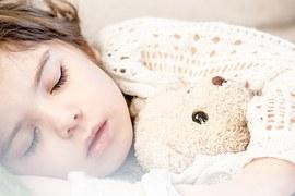 Kind schläft mit Teddybär