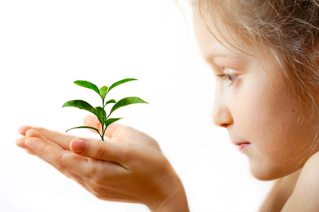 Mädchen hällt Pflanze in der Hand