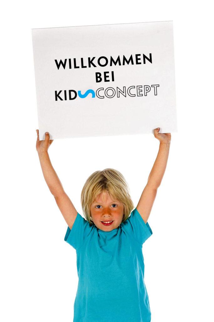 """Junge hällt Schild mit der Aufschrift """"Willkommen bei Kids Concept"""" hoch"""