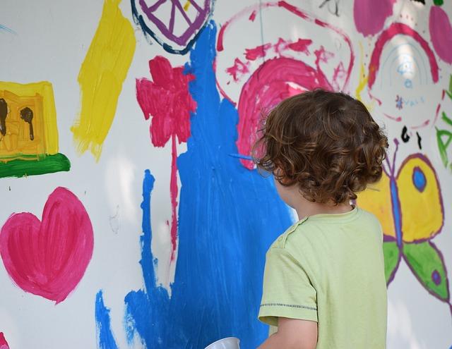 Kind bemalt Wand mit Farben