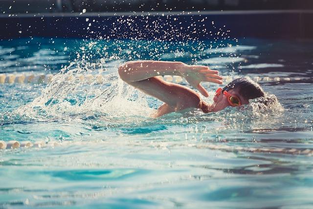 Kind schwimmt im Hallenbad