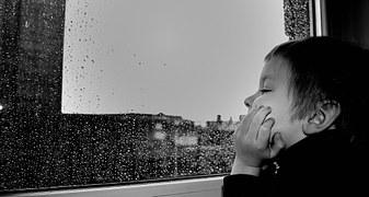 Junge sitzt gelangweilt vor verregnetem Fenster