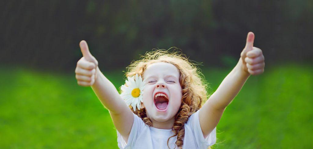 Kind mit Gänseblümchen freut sich und gibt Daumen nach oben